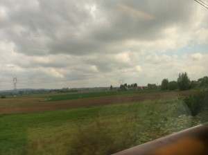 French countryside flashing by at 200 mph, trying to be sunny.